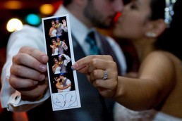 bride and groom holding film strip from photo booth