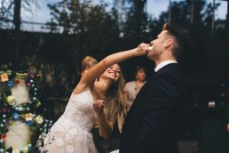Bride shoving cake in grooms face lauging