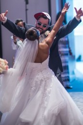 Bride hugging groom wearing hat and sunglasses for grand entrance