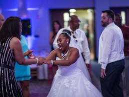 Happy Bride grabbing guests hands to dance at MRCC Banquet and Convention Center Michigan