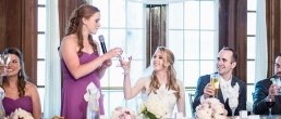Wedding Bridesmaid wearing purple dress giving speeche toasting with bride at table