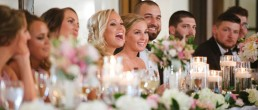 Wedding Party sitting lined up at wedding reception head table with Bridesmaid laughing