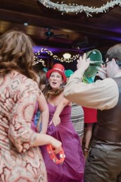 Girl on dance floor wearing red top hat pointing to wedding guests wearing hats