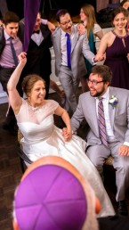 Guests circle around Bride Groom in chairs for Mitzvah Dances