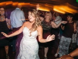 Bride on Dance floor singing with eyes closed guests and blurred orange lights behind