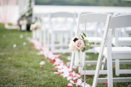 White chairs lined up for outdoor wedding ceremony