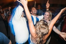 Bride groom and guests in a circle with arms in air dancing